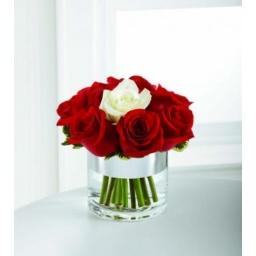 Base de vidrio con rosas rojas y una blanca.