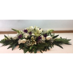 Centro de mesa alargado con flores blancas y lilas