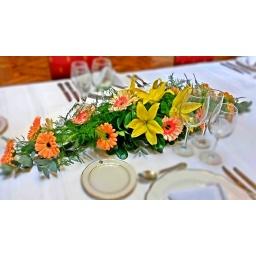 Centro de mesa alargado con gerberas y lilums