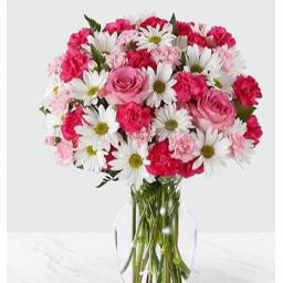 Florero con flores en tonos rosado y blanco